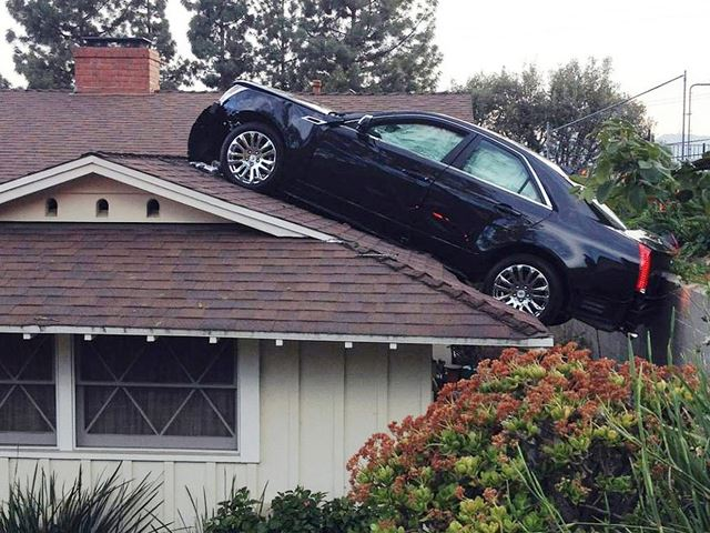 "The car ""parked"" on the roof of the house."